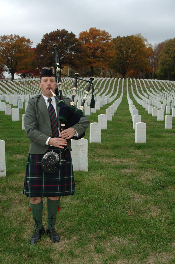Bagpiper Paul Cora piping memorial music on his bagpipes at a Veterans Cemetery